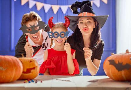 Moeder, vader en hun dochter hebben plezier thuis. Gelukkige familie vieren voor Halloween. Mensen die carnavalkostuums dragen.