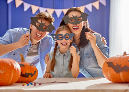 Mother, father and their daughter having fun at home. Happy Family preparing for Halloween.