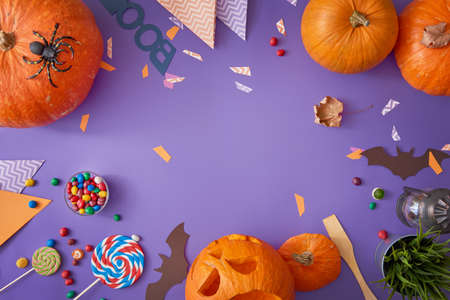 Happy halloween! Carving pumpkin, candy, paper bats on the table in the home. Preparing for holiday. Banco de Imagens