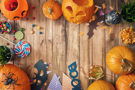 Happy halloween! Carving pumpkin, candy, paper bats on the table in the home. Preparing for holiday. Stock fotó