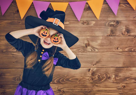 Happy Halloween! Cute little witch with cookies pumpkins.