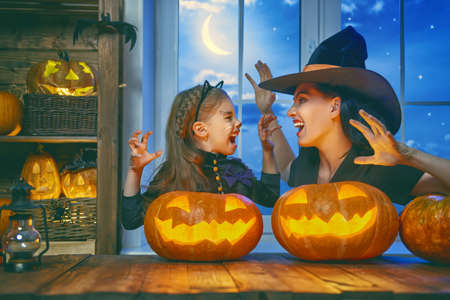Mother and her daughter having fun at home. Happy Family celebrating for Halloween.