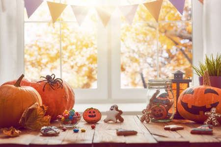 Happy Halloween! Pumpkin, sweets and cookies on the table in the home. Preparation for holiday. Stock Photo