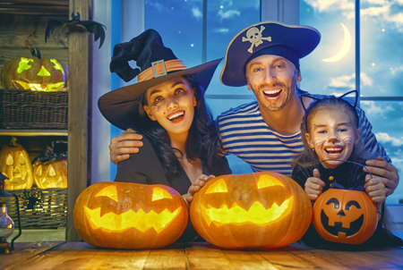 Mother, father and their daughter having fun at home. Happy family celebrating for Halloween. People wearing carnival costumes.