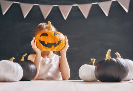 Cute little child with pumpkin. Happy family preparing for Halloween.