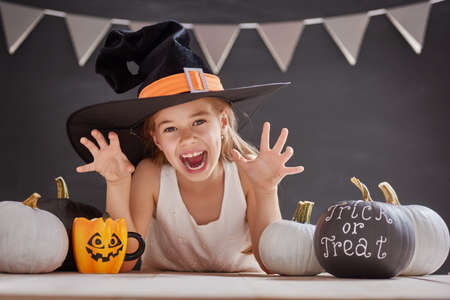 Cute little child with pumpkin. Happy family preparing for Halloween. Girl wearing witch hat. Stock Photo