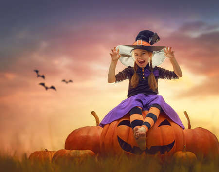 Happy Halloween! Cute little witch with pumpkins. Beautiful young child girl in costume outdoors. Stock Photo