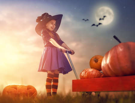 Happy Halloween Cute little witch with pumpkins. Beautiful young child girl in costume outdoors.
