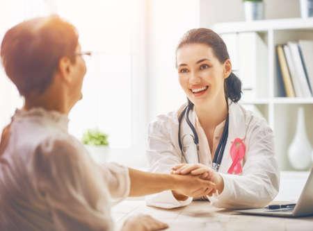 Fita rosa para conscientização do câncer de mama. Paciente do sexo feminino ouvir o médico no consultório médico. Aumentar o conhecimento sobre pessoas que vivem com doenças tumorais. Foto de archivo