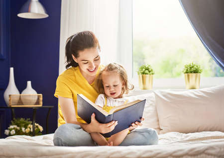 Pretty young mother reading a book to her daughter. Family holiday and togetherness. Standard-Bild