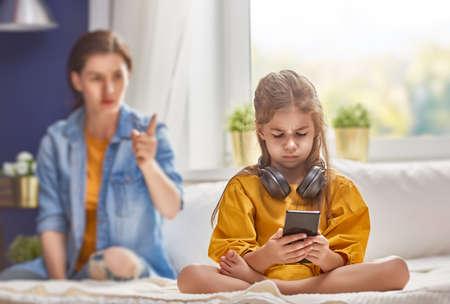 Matka beszta jej dziecko dziewczynka gra na telefonie. Relacje rodzinne.
