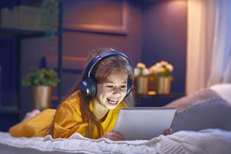 태블릿 및 가정에서 침대에 헤드폰 어린 소녀. 음악을 듣고 자식 소녀입니다.