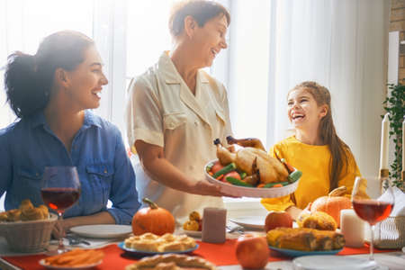 Happy Thanksgiving Day! Autumn feast. Family sitting at the table and celebrating holiday. Traditional dinner. Grandmother, mother and daughter. Stock Photo