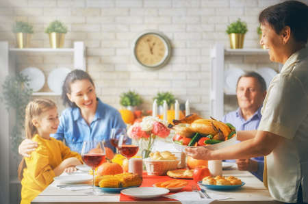 Happy Thanksgiving Day! Autumn feast. Family sitting at the table and celebrating holiday. Grandparents, parents and children. Traditional dinner. Stock Photo