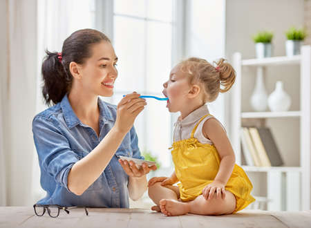 Happy young mother feeding her baby girl with a spoon at home. Stock Photo