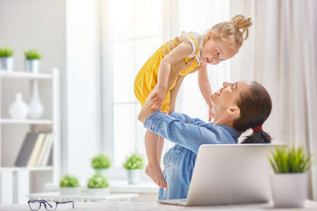 Young mother with toddler child working on the computer from home.