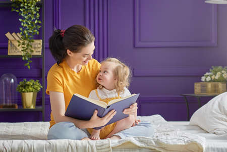 Pretty young mother reading a book to her daughter. Family holiday and togetherness. Stok Fotoğraf