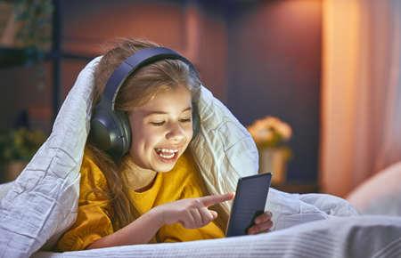 집에서 침대에 헤드폰 어린 소녀. 음악을 듣고 자식 소녀입니다.
