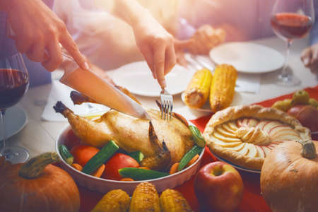 Happy Thanksgiving Day! Autumn feast. Family sitting at the table and celebrating holiday. Traditional dinner. Parents and children.