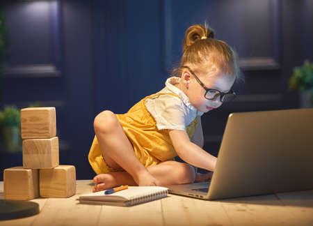 Cute baby girl working on a computer at home. Stockfoto