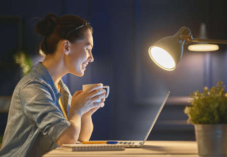 Happy casual beautiful woman working on a laptop at the night at home. Stockfoto