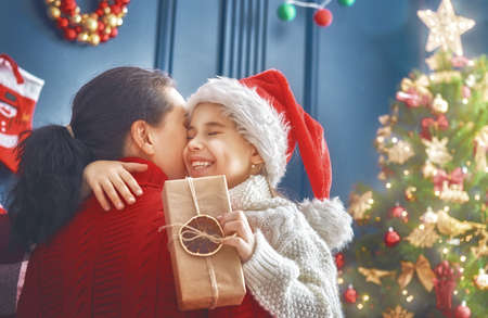 Merry Christmas And Happy Holidays Cheerful Mom Her Cute Daughter Girl Exchanging Gifts