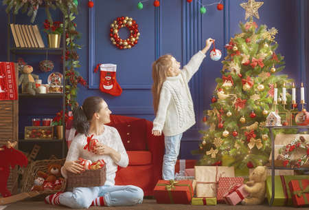 Merry Christmas and Happy Holidays!  Mom and daughter decorate the tree in room. Loving family indoors. Stock fotó