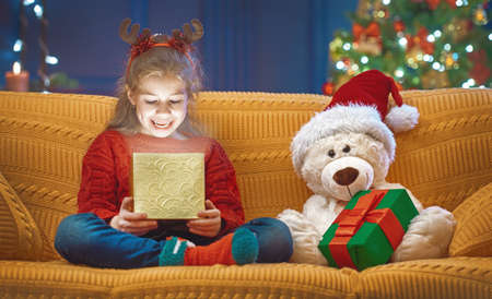 Merry Christmas and Happy Holiday! Cute little child girl with present gift box near tree at home. Stock Photo
