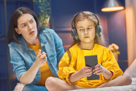 Mother is scolding her child girl playing on phone. Family relationships.