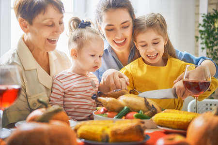 Happy Thanksgiving Day! Autumn feast. Family sitting at the table and celebrating holiday. Traditional dinner. Grandmother, mother and daughter. Stockfoto