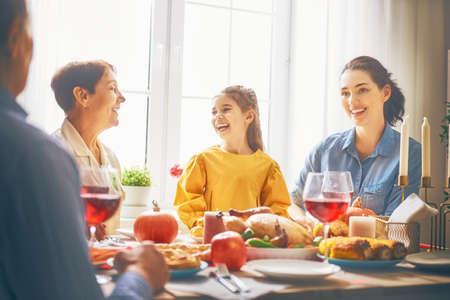 Glücklicher Erntedank-Tag! Herbstfest. Familie, die am Tisch sitzt und Feiertag feiert. Großeltern, Eltern und Kinder. Traditionelles Abendessen.
