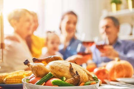 ¡Feliz día de acción de gracias! Fiesta de otoño Familia sentada en la mesa y celebrando las vacaciones. Abuelos, madre, padre e hijo. Cena tradicional Foto de archivo