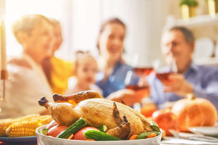 Happy Thanksgiving Day! Autumn feast. Family sitting at the table and celebrating holiday. Grandparents, mother, father and child. Traditional dinner. Banque d'images