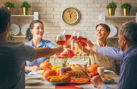 Bonne fête de Thanksgiving! Fête d'automne. Famille assis à la table et célébrant les vacances. Dîner traditionnel Grands-parents, parents et enfants. Les gens et les acclamations. Banque d'images