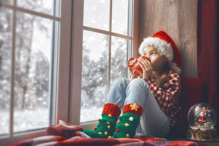 Merry Christmas and happy holidays! Cute little girl sitting by the window with a cup of hot drink and looking at the winter forest. Room decorated. Kid enjoys the snowfall.
