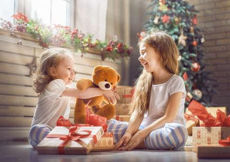 Wesołych Świąt i Wesołych Świąt! Rozochocone śliczne children dziewczyny otwiera prezenty. Dzieci sobie piżamy zabawy w pobliżu drzewa rano. Kochająca rodzina z prezentami w pokoju. Zdjęcie Seryjne