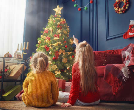 Merry Christmas and Happy Holidays! Cheerful cute little children girls. Kids sisters near tree indoors. Stock Photo