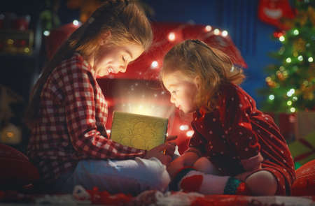 Merry Christmas and Happy Holiday! Cute little children girls with present gift box near tree at home. Stok Fotoğraf