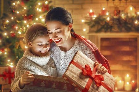 메리 크리스마스와 해피 홀리데이! 사랑하는 가족 어머니와 아이 마법 선물 상자. 스톡 콘텐츠