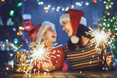 Merry Christmas and Happy Holiday! Mom and daughter having fun near the tree at home. Stock Photo