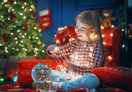 Merry Christmas and Happy Holidays! Cheerful cute little child girl. Kid near tree indoors.