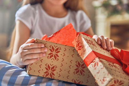 Happy holidays! Cute little child opening gift at Christmas. Close up.