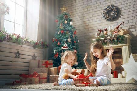 Feliz Navidad y felices fiestas! Alegres niñas lindas para niños abriendo regalos. Niños vistiendo pijamas divirtiéndose cerca del árbol en la mañana. Familia amorosa con regalos en la habitación. Foto de archivo