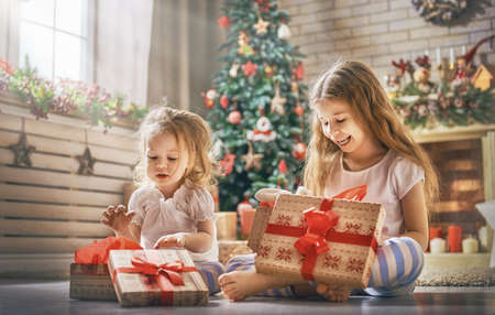 Merry Christmas and Happy Holidays! Cheerful cute childrens girls opening gifts. Kids wearing pajamas having fun near tree in the morning. Loving family with presents in room.