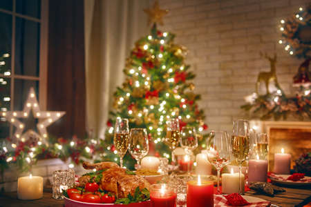 Merry Christmas and Happy New Year! A beautiful living room decorated for holidays. Table served to the dinner. Stockfoto