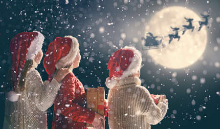 Merry Christmas and happy holidays! Cute little children with xmas presents. Santa Claus flying in his sleigh against moon sky. Kids enjoying the holiday with gifts on dark background. Stock Photo