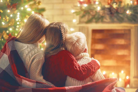 Merry Christmas and Happy Holiday! Cute little children looking at fireplace near tree at home.  Archivio Fotografico