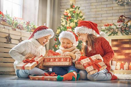 Wesołych Świąt i Wesołych Świąt! Rozochoceni śliczni dzieci otwiera prezenty. Dzieciaki ma zabawę blisko drzewa w ranku. Kochająca rodzina z prezentami w pokoju.
