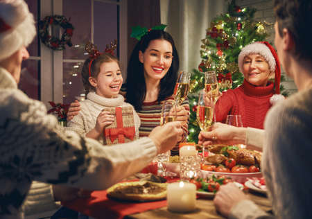 Merry Christmas! Happy family are having dinner at home. Celebration holiday and togetherness near tree. Stok Fotoğraf - 89630394