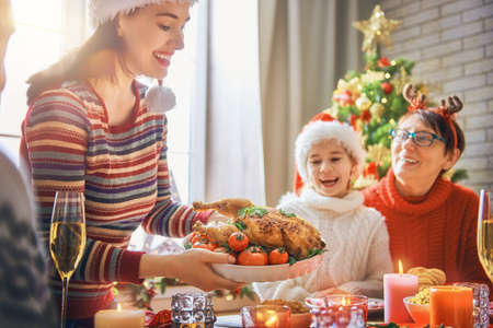 the grand daughter: Merry Christmas! Happy family are having dinner at home. Celebration holiday and togetherness near tree.
